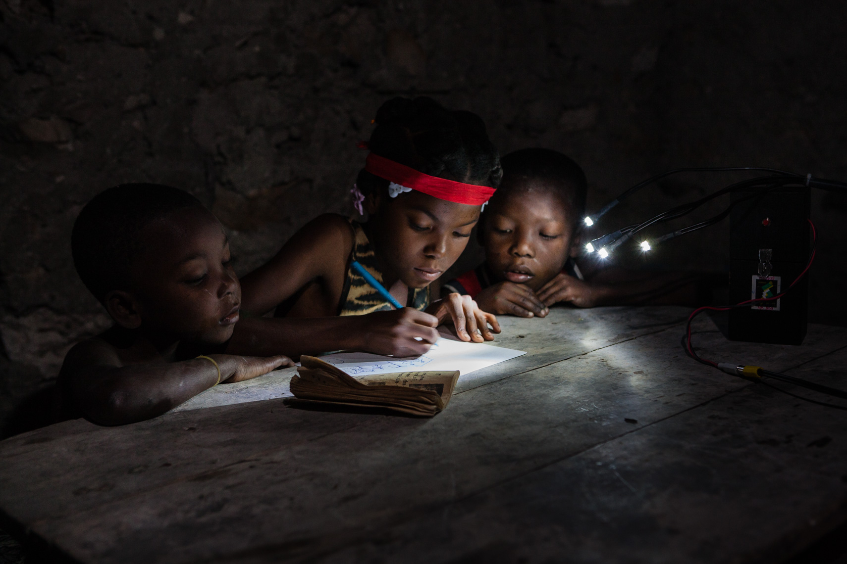 Three haitian ki9ds do home work